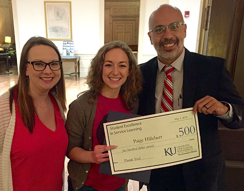Three people holding an award certificate and an imitation $500 check.