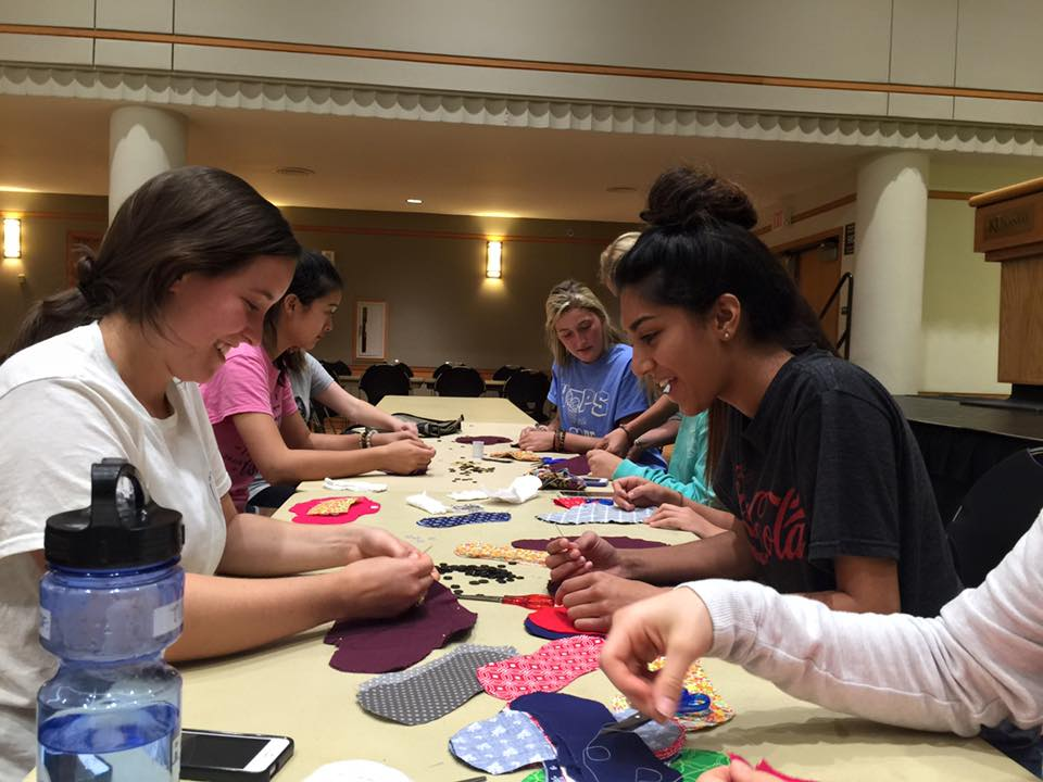 Students from MEDLIFE KU hold a workshop to make reusable pads for women in communities lacking hygiene resources.